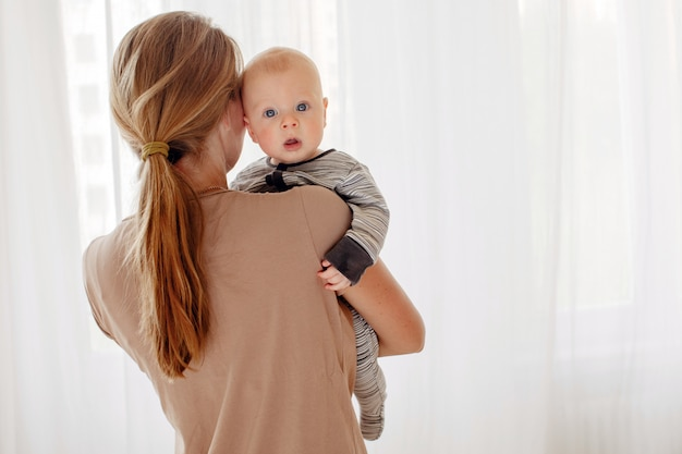 Back view of mother holding cute big-eyed kid on hands against white curtain in light room