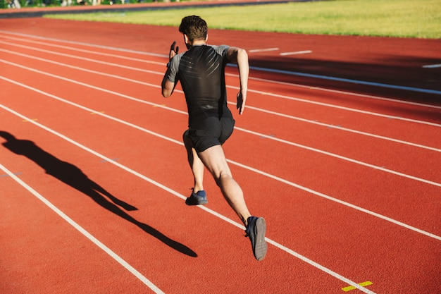 Back view of motivated young sportsman running