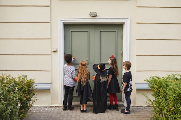 Back view at multi-ethnic group of kids wearing halloween costumes ringing doorbell while trick or treating together, copy space