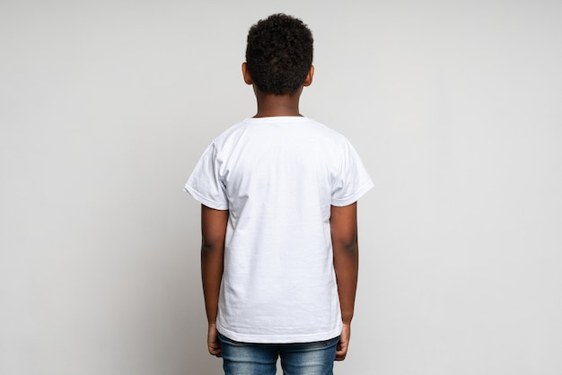 Back view of the multiracial boy wearing white t shirt. childhood concept. isolated on white background, studio shot