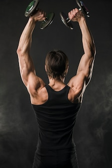 Back view of muscled man lifting up weights