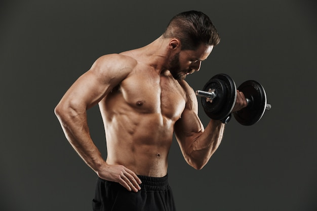 Back view of a muscular bodybuilder lifting heavy dumbbell
