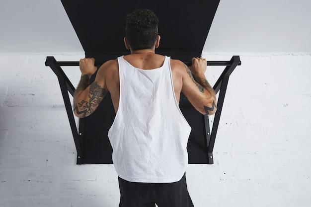 Vista posteriore su atleta maschio muscoloso in t-shirt serbatoio vuoto bianco che mostra le mosse calisthenic tirare su il pullbar, tenendo in cima