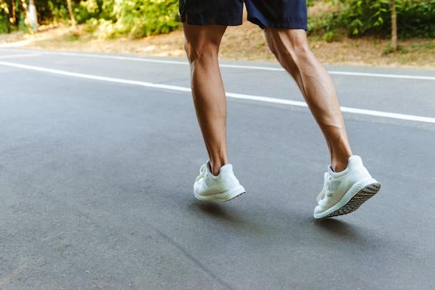 Back view of muscular sportsman legs jogging