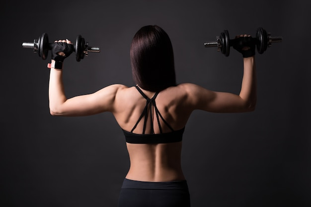 Back view of muscular woman with dumbbells posing over black background