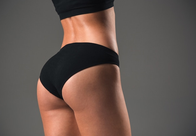 The back view of muscular young woman athlete posing on gray studio background