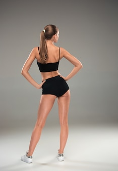The back view of muscular young woman athlete posing on gray