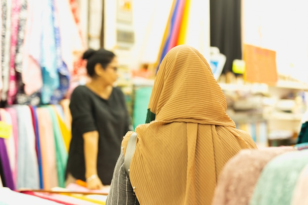 Back view of muslim woman with cream hijab choosing fabrics at market.