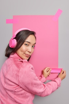 Back view of mysterious young asian woman plasters pink sheet of paper on grey wall to place your advertisement listens music wears jacket looks seriously