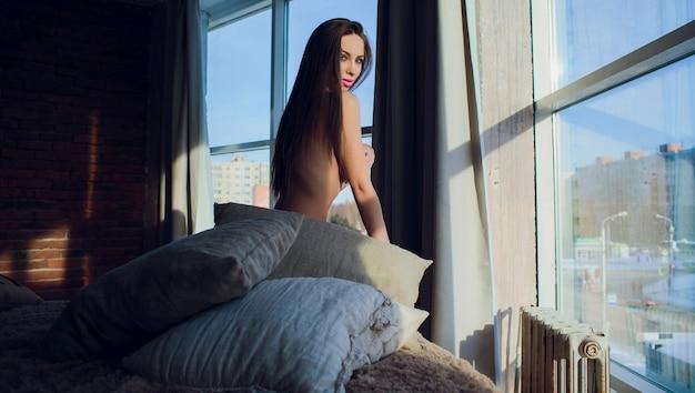 Вид сзади голая блондинка смотрит в окно и играет со своими волосами, сидя на кровати