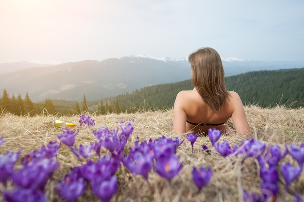 Back view of naked woman in swimsuit is lying on the spring grass nearly crocuses in the mountain