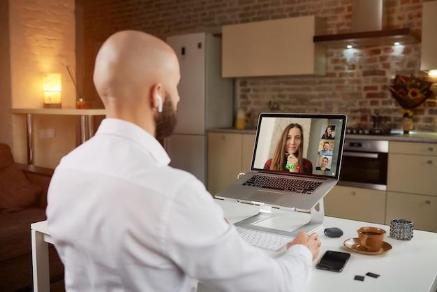 Вид сзади лысого сотрудника-мужчины в наушниках, который работает удаленно, слушая своих коллег на бизнес-видеоконференции на ноутбуке.