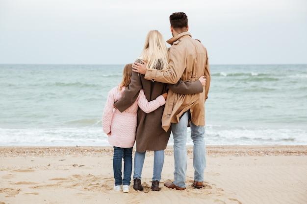 一緒にビーチで楽しんで小さな娘と美しい家族の背面図