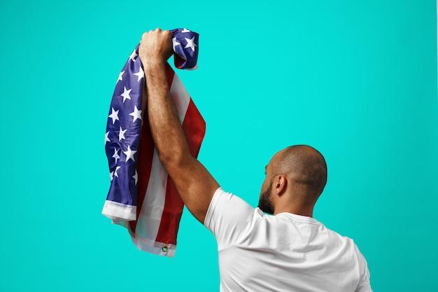Вид сзади черного человека, держащего флаг сша