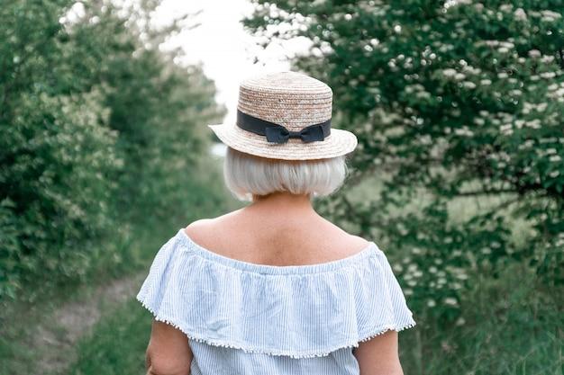 Вид сзади блондинка в соломенной шляпе с бантиком в летнем саду