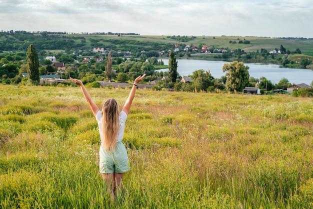 호수와 흐린 하늘 태양이 있는 여름 초원 여름 시골 풍경에 금발 소녀의 뒷모습...