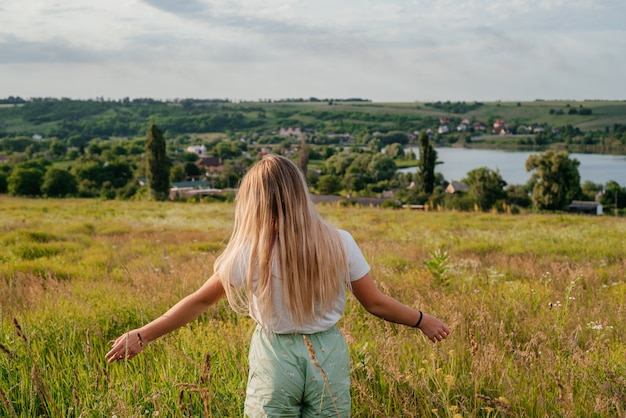 여름 초원에 금발 소녀의 뒷모습, 호수와 흐린 하늘이 있는 여름 시골 풍경. 따뜻하고 아름다운 여름날에 잔잔한 물에 의해 일몰 저녁 빛. 여름 배경