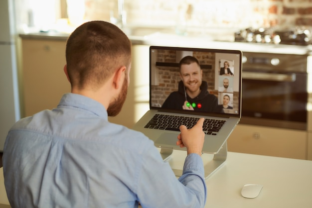 Вид сзади босса, который слушает своего сотрудника на видео-встрече на ноутбуке