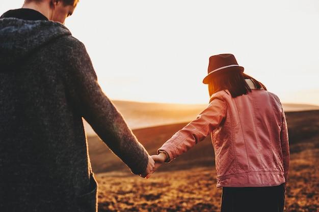손을 잡고 소녀가 휴가 시간에 일몰에 대해 그녀의 남자 친구를 이끌고있는 동안 여행하는 백인 부부의 다시보기.