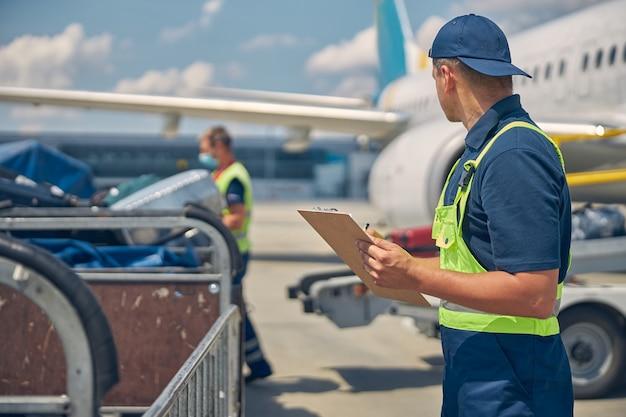 Вид сзади на кавказского рабочего, следящего за загрузкой багажа на конвейер