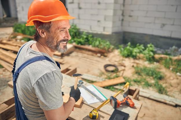 手にハンマーを持って目をそらしている陽気な男性労働者の背面図