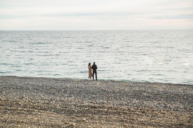 ビーチで太陽を抱き締めて見ているカップルの背面図。春または秋。