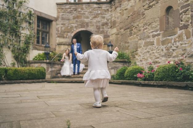 かわいい女の赤ちゃんの背面図は両親に向かって走ります