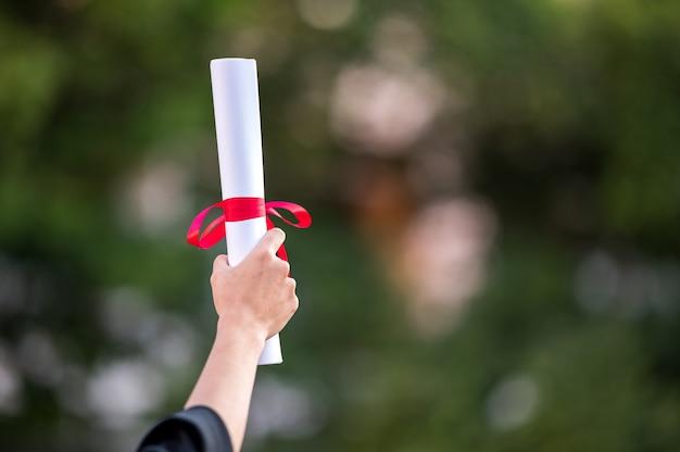 卒業証書を保持している大学の学位を持つ女性卒業生の背面図