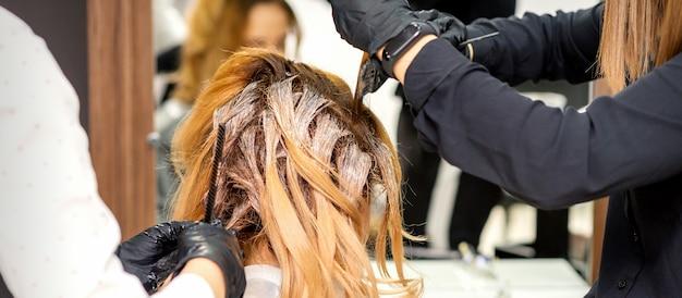 Вид сзади девушки-парикмахера в перчатках, окрашивающих волосы рыжей молодой женщины светлой или белой краской в салоне красоты