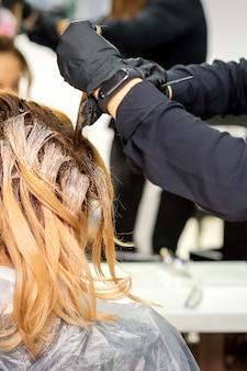 뷰티 살롱에서 빛 또는 흰색 염료와 빨간 머리 젊은 여자의 머리를 착색 장갑에 여성 미용사의 다시보기