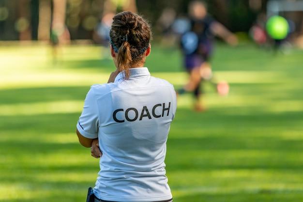 彼女のチームが屋外のサッカー場で競っているのを見ている女性のスポーツコーチの背面図