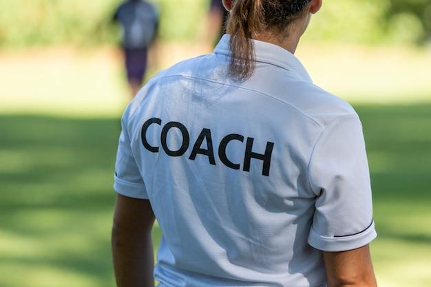 屋外スポーツフィールドで競っている彼女のチームを見ている女性スポーツコーチの背面図