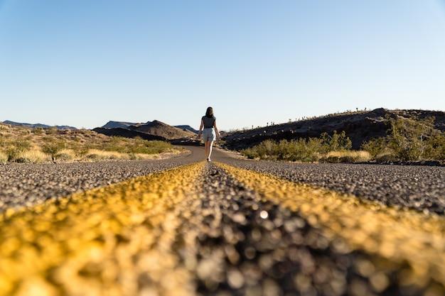 Вид сзади женщины, идущей по дороге, увлекательная поездка в аризону по шоссе 6