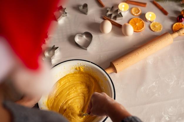 그릇에 반죽을 만드는 빨간 산타 모자에있는 여자의 뒷면