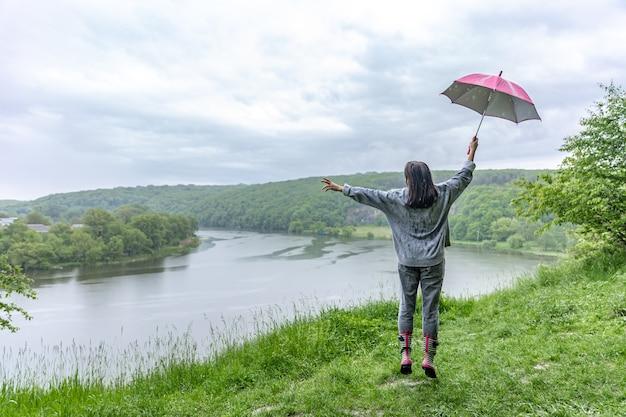 雨天の山岳地帯の湖の近くでジャンプする傘の下の女の子の背面図