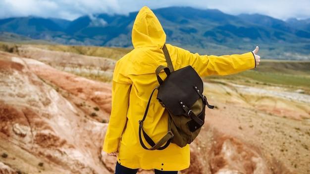 休暇旅行で色の山の美しい場所でバックパックを持った女の子の背面図。旅行とリラクゼーションのコンセプト