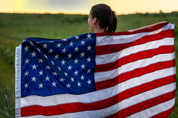 野原の芝生の上を走っているアメリカの国旗を持つ少女の背面図