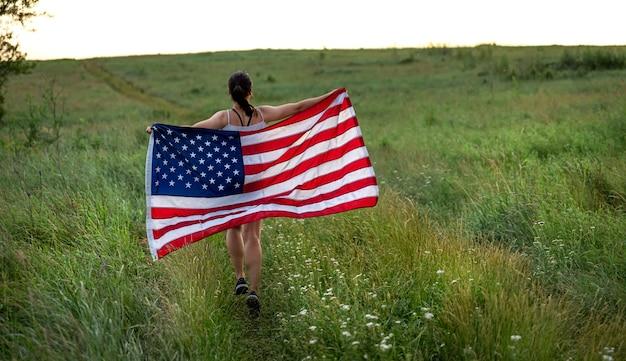 Вид сзади девушки с американским флагом, бегущей по траве в поле