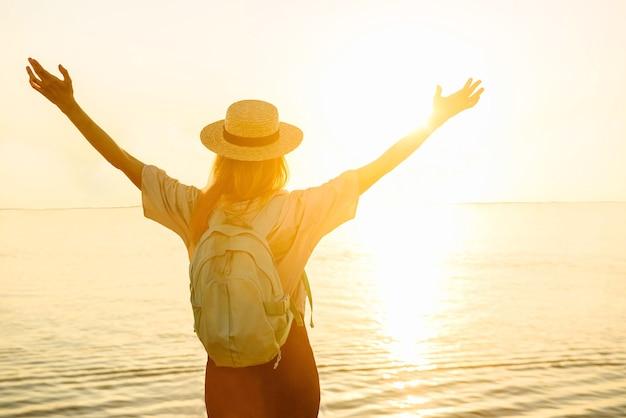 배낭을 메고 행복한 여성 등산객의 뒷모습은 바다 배경에서 일몰에 즐겁게 손을 들었습니다. 여름 여행 및 모험 개념