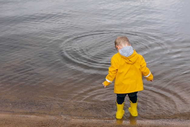 Вид сзади маленького мальчика в желтом плаще и резиновых сапогах стоит и смотрит на воду на сан