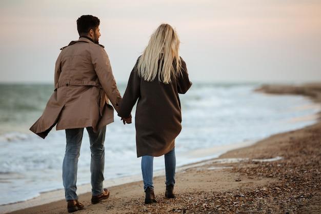 手を繋いでいる素敵なカップルの背面図