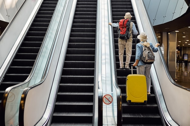공항 터미널에서 에스컬레이터를 올라가는 남자와 여자의 뒷모습