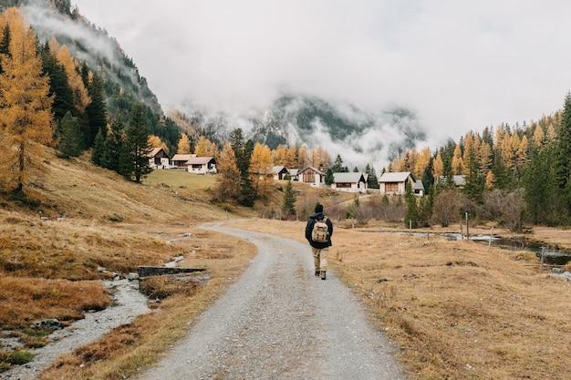 秋の自然の風景に囲まれた歩道に沿って歩くバックパックと男のハイカーの背面図