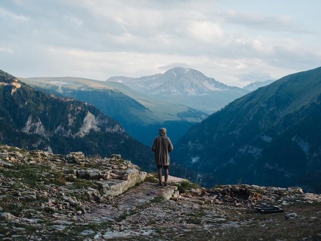 Вид сзади человека в теплой одежде в горах на природе.
