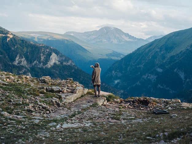 自然の山の中で暖かい服を着た男の背面図。