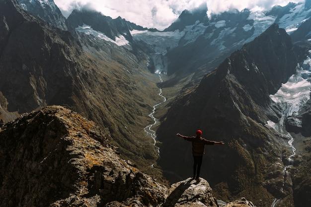 Вид сзади человека, стоящего на фоне гор с раскинутыми руками. мужчина в горах поднимает руки. человек на фоне гор. путешествие в горы