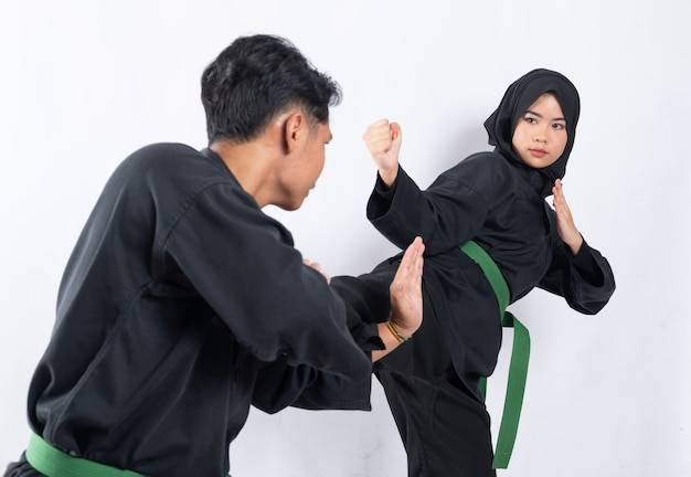 베일에 아시아 여성의 발차기를 차단하는 움직임으로 서있는 pencak silat 유니폼을 입은 남자의 뒷모습