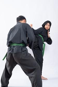 ベールでアジアの女性のキックをブロックする動きで立っているプンチャックシラットの制服を着た男性の背面図