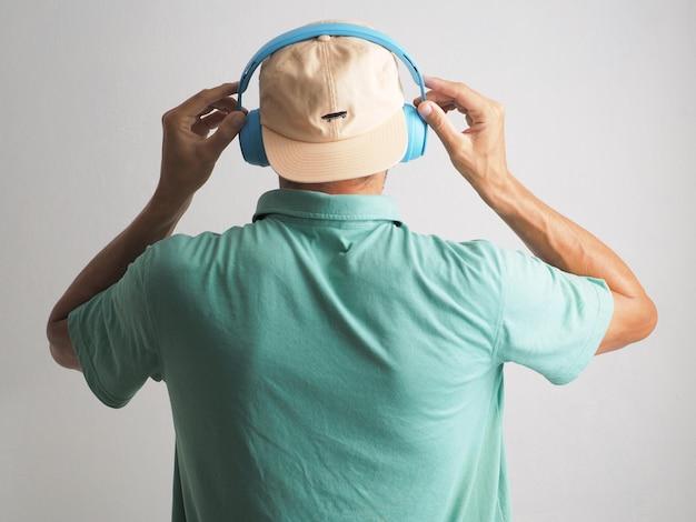파란색 무선 헤드폰과 모자를 쓰고 흰 벽에 기대어 음악을 듣는 남자의 뒷모습.