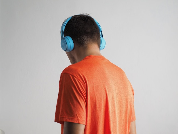 파란색 무선 헤드폰과 주황색 티셔츠를 입고 음악을 듣고 있는 남자의 뒷모습.